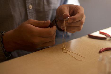 Atelier créateur bijoux fantaisie Shango travaillant un collier plaqué or avec pierre semi-précieuse